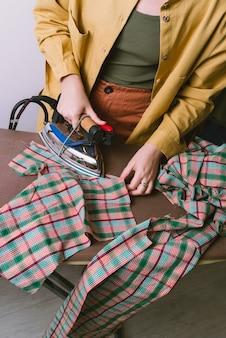 Kobieta prasowanie tkaniny w kratę w szwalni, selektywne focus