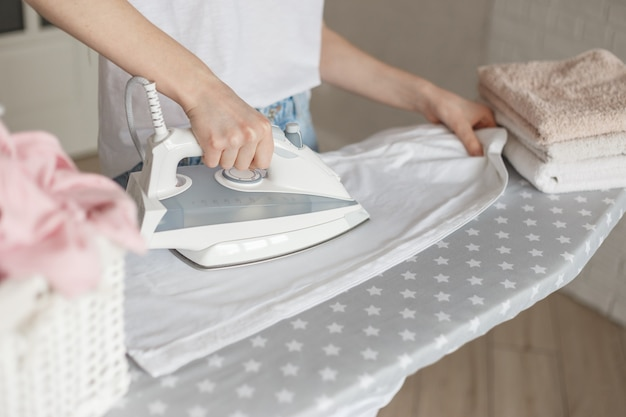 Kobieta prasująca białą praną koszulę w domu. wiklinowy kosz i stos kolorowych ręczników na desce do prasowania