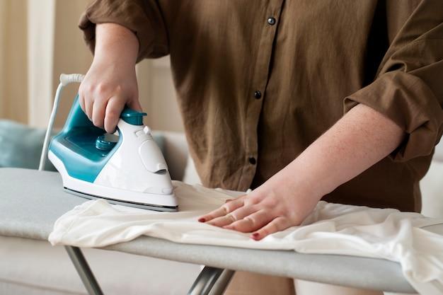 Kobieta prasująca koszulkę prace domowe w pralni