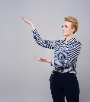 Kobieta prezentuje coś po swojej prawej stronie