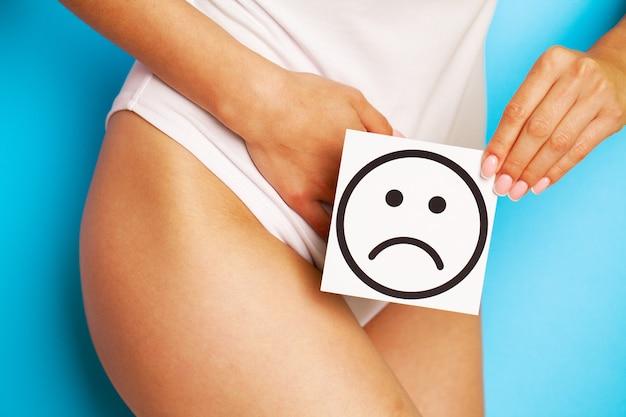Kobieta problem zdrowotny, zaburzenia trawienne, bóle miesiączkowe, problemy zdrowotne koncepcja. kobieta o sprawnym szczupłym ciele w majtkach, posiadająca kartę ze smutną buźką przy brzuchu