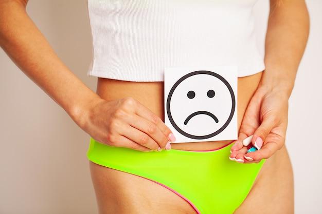 Kobieta problem zdrowotny, zaburzenia trawienne, bóle miesiączkowe, problemy zdrowotne koncepcja. kobieta o sprawnym szczupłym ciele w majtkach, posiadająca kartę ze smutnym uśmiechem przy brzuchu.