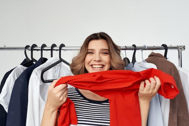 Kobieta próbuje na czerwonej koszuli na białym tle