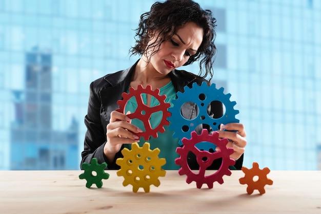 Kobieta próbuje połączyć koła zębate koncepcja współpracy i integracji w pracy zespołowej