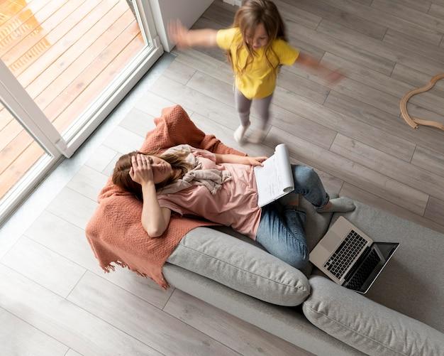 Kobieta próbuje pracować na laptopie w domu, podczas gdy jej dzieci biegają po okolicy