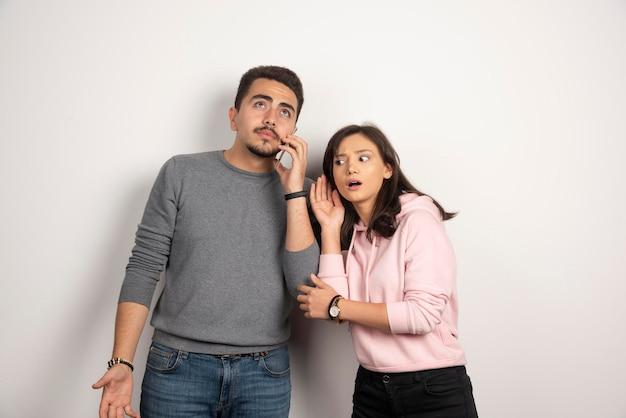 Kobieta próbuje słuchać, co chłopak rozmawia przez telefon.