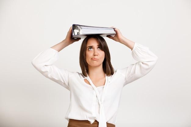 Kobieta próbuje trzymać stosy dokumentów na głowie