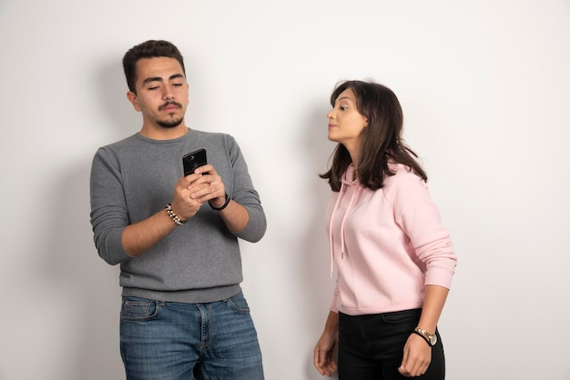 Kobieta próbuje zajrzeć do swojego telefonu na białym tle.