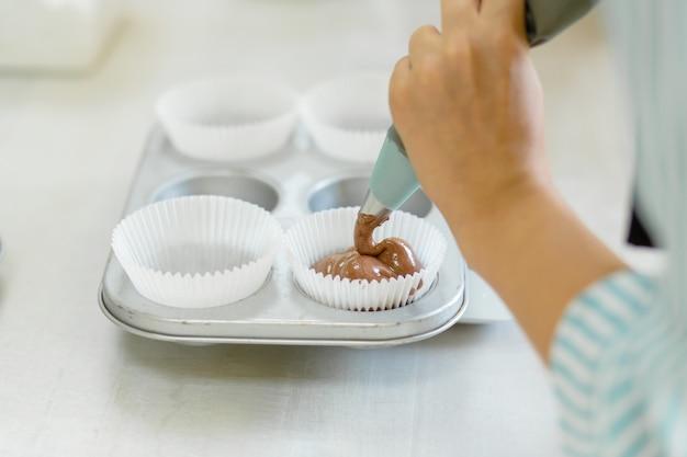 Kobieta profesjonalny cukiernik rozprzestrzenia ciasto czekoladowe w naczyniu do pieczenia