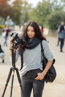 Kobieta profesjonalny fotograf robienia zdjęć krajobrazu aparatem dslr i statywem na zewnątrz.