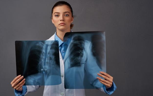 Kobieta profesjonalny lekarz z prześwietleniem rentgenowskim na szarym tle przycięty widok. wysokiej jakości zdjęcie