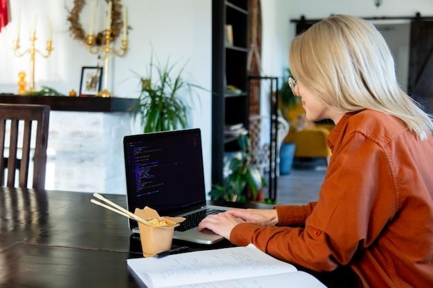 Kobieta programista pracująca z komputerem w domowym biurze