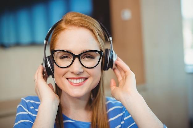 Kobieta projektant graficzny słuchanie muzyki na słuchawkach