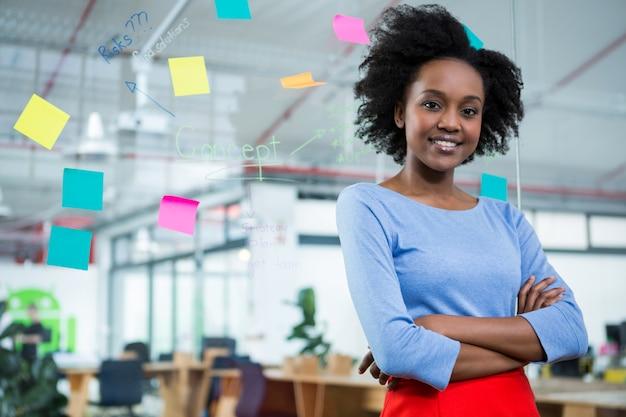 Kobieta projektant graficzny stojący z rękami skrzyżowanymi w biurze kreatywnym
