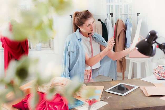 Kobieta projektant mody, pracująca w studio, siedząc na biurku