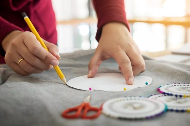Kobieta projektant mody pracy ze szkicami w studio i wybierając tkaniny postępu na stół krawiec.