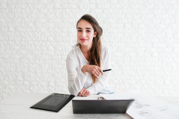 Kobieta projektant patrząc na kamery w miejscu pracy