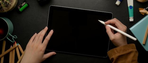 Kobieta projektant rysunek na cyfrowym tablecie z rysikiem na ciemnym stole roboczym z narzędziami do malowania