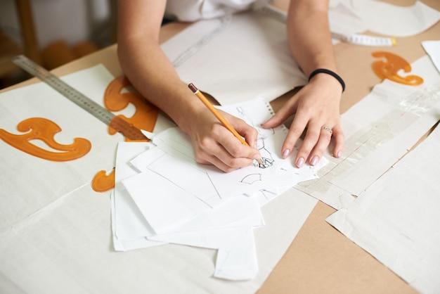 Kobieta projektant rysunek szkice ołówkiem odzieży