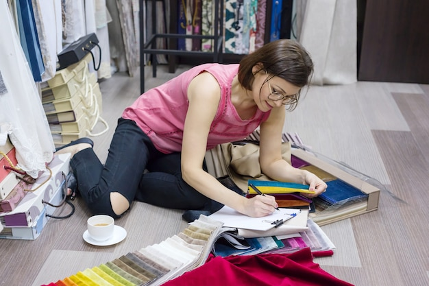 Kobieta projektant wnętrz, pracuje z próbkami tkanin na zasłony i rolety.
