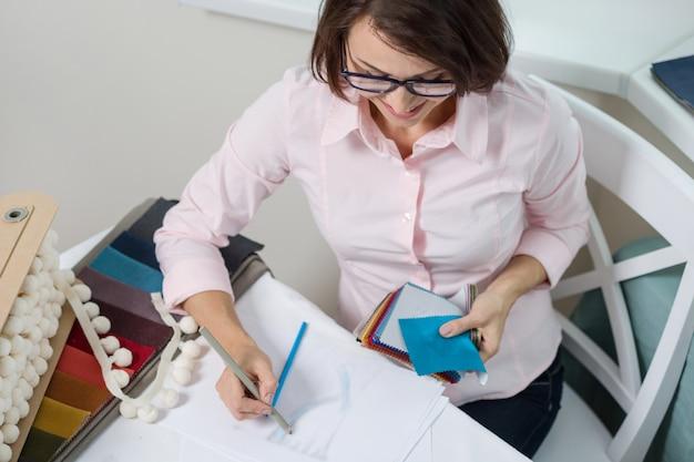 Kobieta projektant wnętrz, pracuje z próbkami tkanin