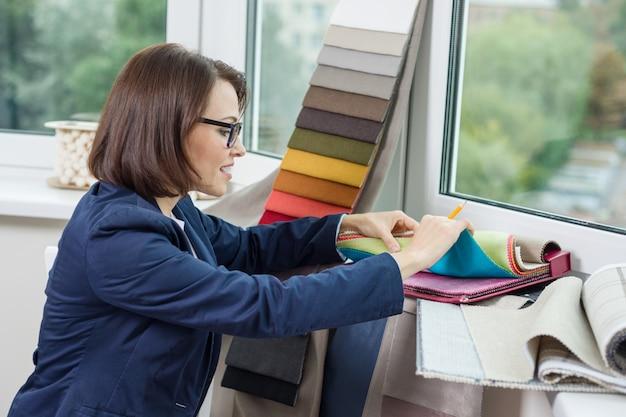 Kobieta projektant wnętrz, współpracuje z próbkami tkanin na zasłony
