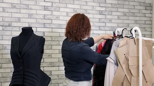 Kobieta projektantka mody w warsztacie wybiera ubrania powiesić na wieszakach w atelier.