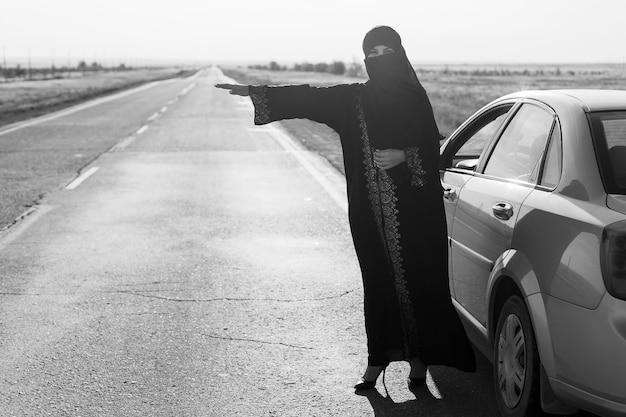 Kobieta prosi o pomoc na drodze, muzułmanka w tradycyjnym stroju. czarny i biały