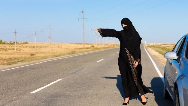Kobieta prosi o pomoc na pustej drodze y