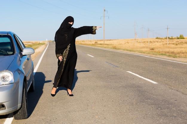 Kobieta prosi o pomoc na pustej drodze.