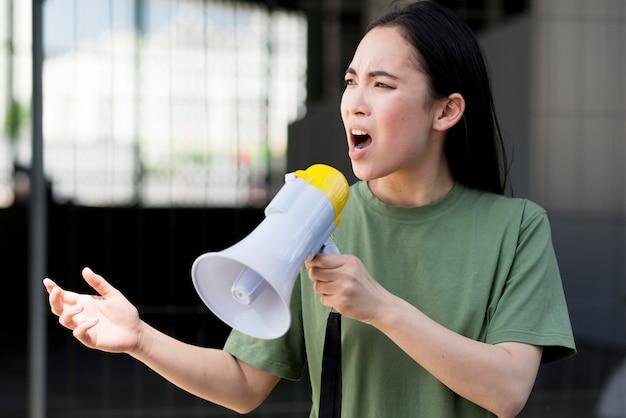 Kobieta protestuje i opowiada na megafonie
