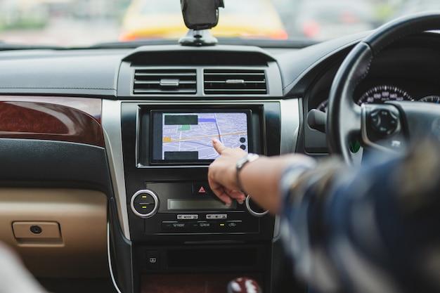 Kobieta prowadząca samochód ręką dotykając nawigacji na ekranie monitora.