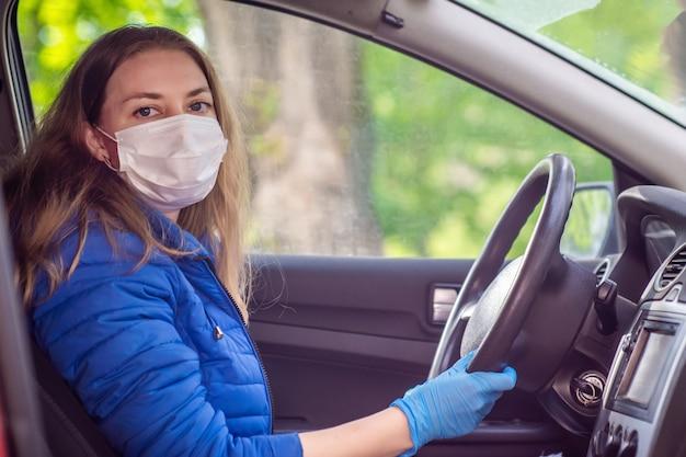 Kobieta prowadząca samochód w ochronnej masce medycznej i rękawiczkach. styl życia i bezpieczna jazda podczas pandemicznego koronawirusa w kwarantannie