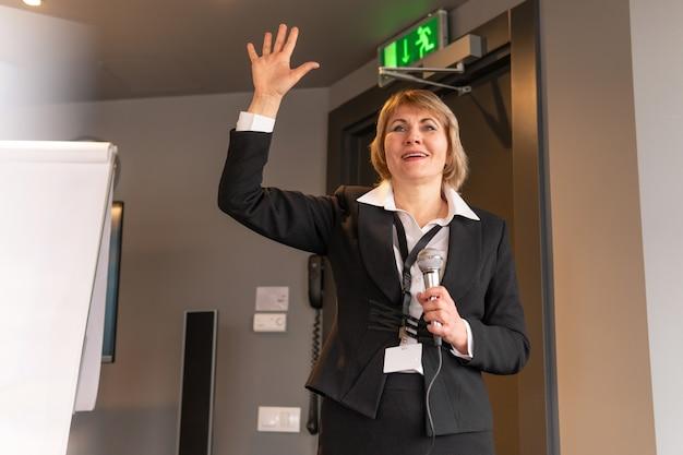 Kobieta prowadzi szkolenia w centrum biznesowym. kobieta w średnim wieku mówi do mikrofonu.