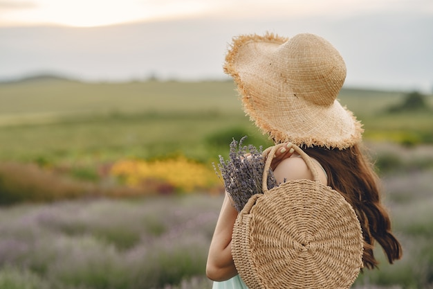 Kobieta prowansji relaks w lawendowym polu. dama w słomkowym kapeluszu. dziewczyna z torbą.