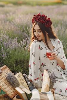 Kobieta prowansji relaks w lawendowym polu. pani na pikniku. kobieta w wieńcu kwiatów.