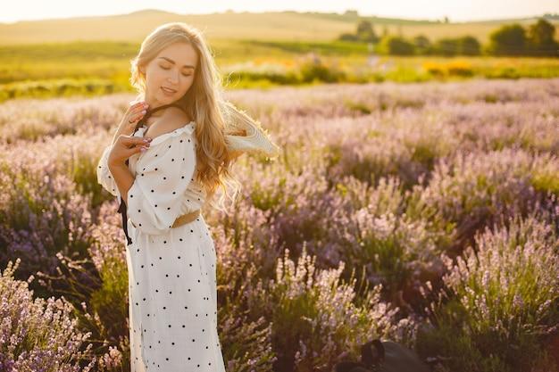 Kobieta prowansji relaks w lawendowym polu. pani w białej sukni. dziewczyna w słomkowym kapeluszu.