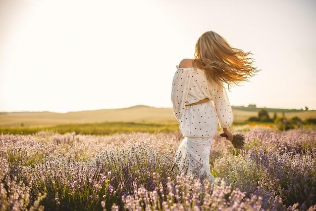 Kobieta prowansji relaks w lawendowym polu. pani w białej sukni. dziewczyna z bukietem kwiatów.