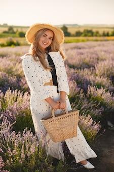 Kobieta prowansji relaks w lawendowym polu. pani w białej sukni. dziewczyna z słomianym kapeluszem i koszem.
