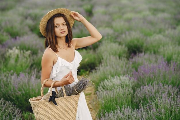 Kobieta prowansji relaks w lawendowym polu. pani w białej sukni. dziewczyna z torbą.