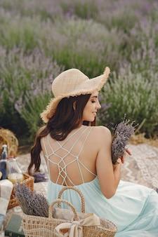 Kobieta prowansji relaks w lawendowym polu. pani w niebieskiej sukience i słomkowym kapeluszu.
