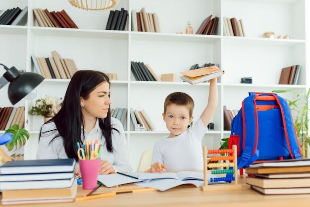 Kobieta prywatny nauczyciel pomaga młodemu studentowi w odrabianiu prac domowych przy biurku w jasnym pokoju dziecka