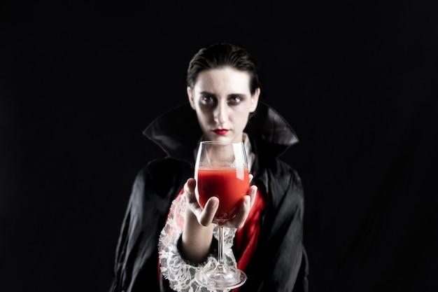 Kobieta przebrana za wampira na halloween trzyma kieliszek czerwonego napoju. studio strzałów w dramatycznych światłach młodej kobiety w kostiumie draculi na czarnym tle