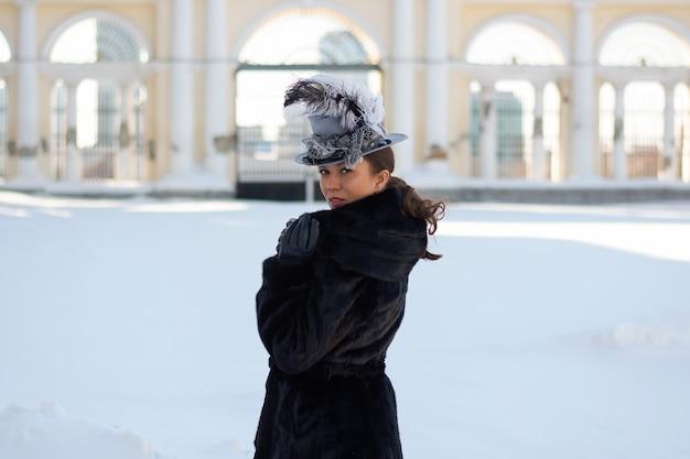 Kobieta przebrana za xix-wieczną szlachciankę stoi w pobliżu starego dworu.rosyjska zima