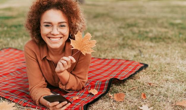 Kobieta przebywa na kocu z miejsca na kopię jesienią