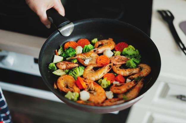 Kobieta przebywa w domu kuchnia i gotowanie krewetek z warzywami na patelni. gotowanie w domu lub koncepcja zdrowego gotowania