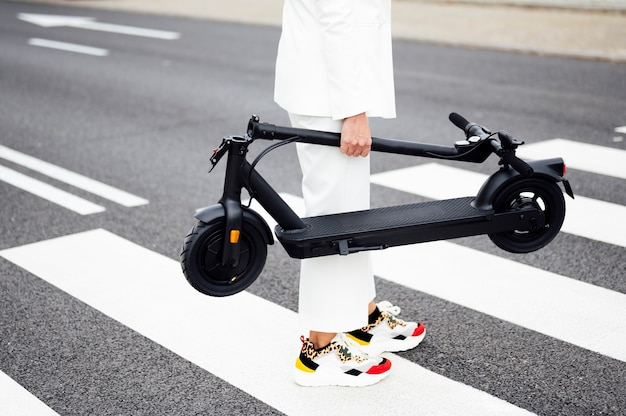 Kobieta przechodząca przez ulicę ze skuterem elektrycznym