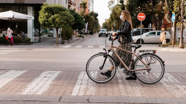 Kobieta przechodzi przez ulicę obok swojego roweru
