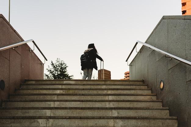 Kobieta przeciągając walizkę na wózek, aby wspiąć się po schodach metra.