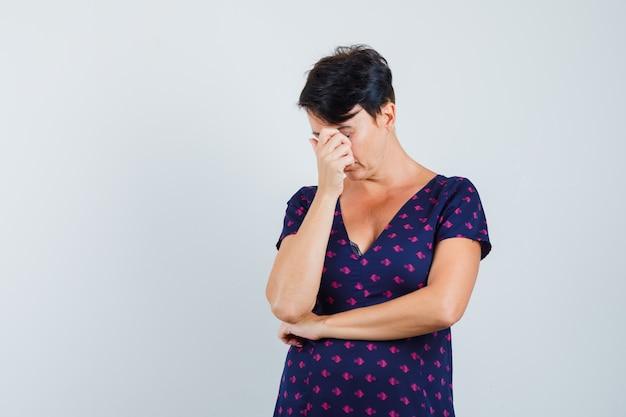 Kobieta przeciera oczy i nos w sukience i wygląda na zmęczoną.
